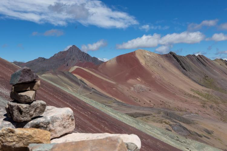 Cairn atop Vinicunca with Jatunrritioc mountain in the background, Vilcanota mountain range, Peru