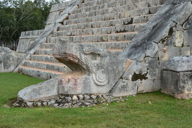 A feathered serpent sculpture at the base of one of the stairways of El Castillo, Chichen-Itza, Mexico